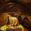 Wine cellar with glasses of white wine against wine barrels — Stock Photo #30487821
