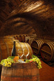 Wine cellar with glasses of white wine against wine barrels — Stock Photo