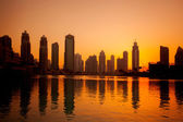Dubai with golden silhouette of downtown against lagoon in United Arab Emirates — Stok fotoğraf