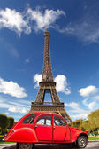 Eiffel Tower with red old car in Paris, France — Stockfoto