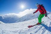 Skidåkare skidåkning slalom i höga berg under solig dag — Stockfoto