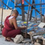 Buddhist monk choosing book on street market. Yangon. Myanmar. — Stock Photo