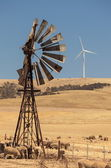 Old broken wind pump and new wind generators distorted by hot air. South Australia. — Stock Photo