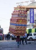Man carries pile of foam mattresses in Merkato market. Addis Aba — Stock Photo