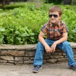 Handsome and happy boy sitting on a retaining wall — Stock Photo