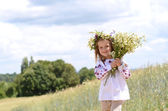 Cute girl in wheat field with bunch of flowers — Stock Photo