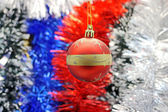 Christmas toy against the background of new year's tinsel — Stock Photo