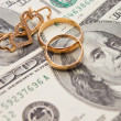 Wedding rings, gold chain and earrings in the form of hearts lie on money — Stockfoto