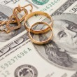 Wedding rings, gold chain and earrings in the form of hearts lie on money — ストック写真