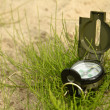 Stock Photo: Soldier's compass lies in bundle of grass on beach