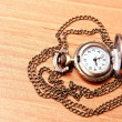 Pocket watch chain on the background of a wooden Desk — Photo
