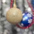Two Christmas tree bulb hanging on a background of new year's tinsel — Stock Photo