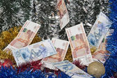 Christmas tinsel and banknotes of rubles. — Stock Photo