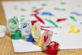 Multicolored jars with gouache and a children's drawing — Stock Photo