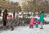 Children and parents on a walk feed the pigeons in the Park in the winter. — Stock Photo