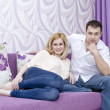 A happy young couple in jeans sitting on the couch in a lilac room — Stock Photo #41141573