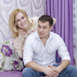 A happy young couple in jeans sitting on the couch in a lilac room — Stock Photo