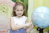 Little girl showing country on the globe — Stock Photo