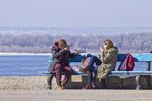 Joven pareja de enamorados en un día soleado primaveral comiendo medialunas en un banco del parque — Foto de Stock