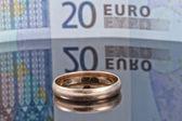 リフレクションによるユーロ紙幣の背景に金の指輪 — ストック写真