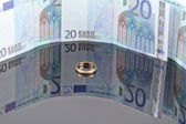Gold ring on background of Euro banknotes with reflection — Stock Photo