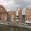 Gdansk in Poland, Modern architecture linked to the medieval town houses next to an old wooden crane of 13-th century on the Motlawa waterfront. — Stock Photo #46465749