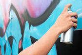 Hand holding spray paint on the wall graffiti — Stock fotografie