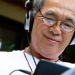 Senior man enjoying music on his tablet — Stock Photo #36309571