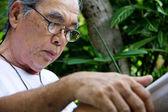 Senior man reading E-book on his tablet. — Photo