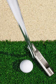 Golf ball and putter on green grass — Stock Photo