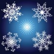 Vector de stock : Set of white snowflakes on blue background