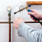 Plumber soldering pipe — Stock Photo