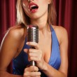 Beautiful singer singing with a retro microphone - Stock Photo