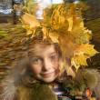 Cute little girl with autumn leaves in the autumn park — Stock Photo