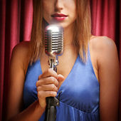 Beautiful singer singing with a retro microphone — Stock Photo