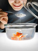 Smiling face above a bowl with a goldfish — Stock Photo
