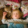 Little girl sleeps on bed with a cat - Stock Photo