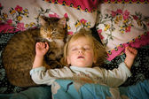 Little girl sleeps on bed with a cat — Stock Photo