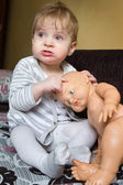 Baby girl with baby doll — Stock Photo