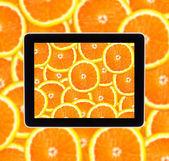 Orange on tablet computear screen — Stock Photo