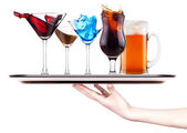 Alcoholic cocktail set with splash on a tray with hand — Stock Photo