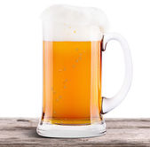 Frosty fresh beer with foam isolated on wooden table — Stock Photo
