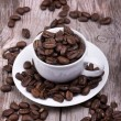 White cup of espresso full of coffee beans — Stock Photo #26361539