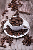 White cup of espresso full of coffee beans — Stock Photo