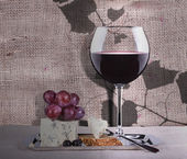 Grapes with wine glass and cheese — Stockfoto