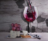 Grapes with wine glass and cheese — Stock Photo