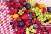 Tasty summer fruits on a red tablecloth — Stock Photo
