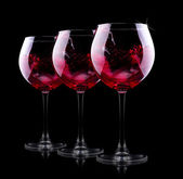 Glass of red splashing wine — Stock Photo