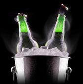 Beer bottles in ice bucket — Stock Photo