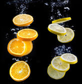 Slice of orange and lemon in the water — Stock Photo